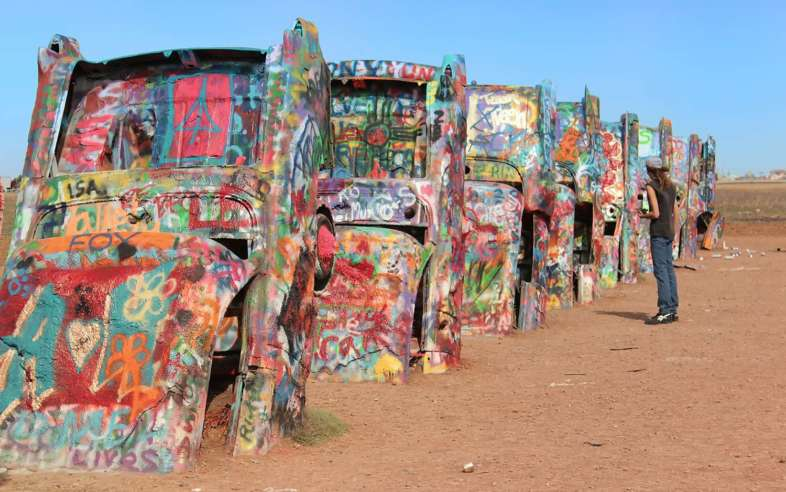 Os carros grafitados e enterrados no chão do Cadillac Ranch em Amarillo, Texas