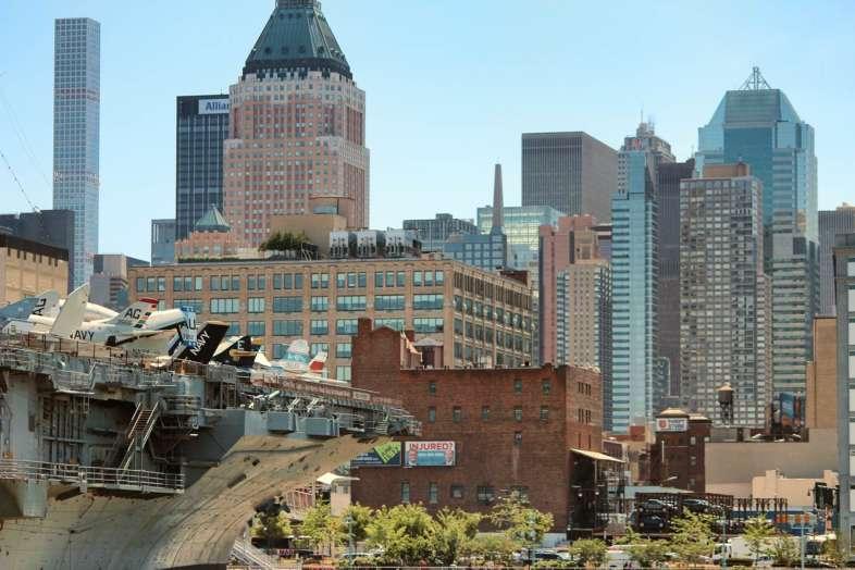 O U.S.S. Intrepid visto do Pier 84 e a cidade de Nova York ao fundo