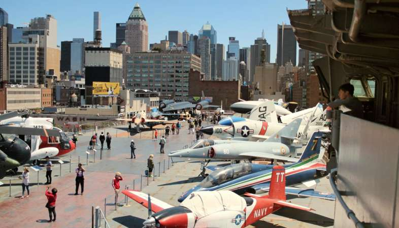 O convés superior do Intrepid está repleto de aviões e helicópteros de diversos períodos do século XX