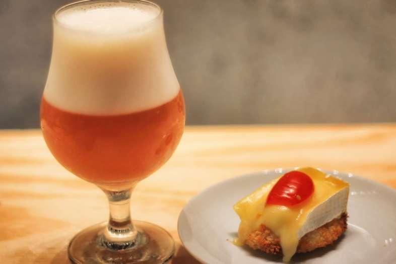Bapa de peito de frango empanado coberto com brie e tomate cereja, acompanhada de cerveja de trigo belga
